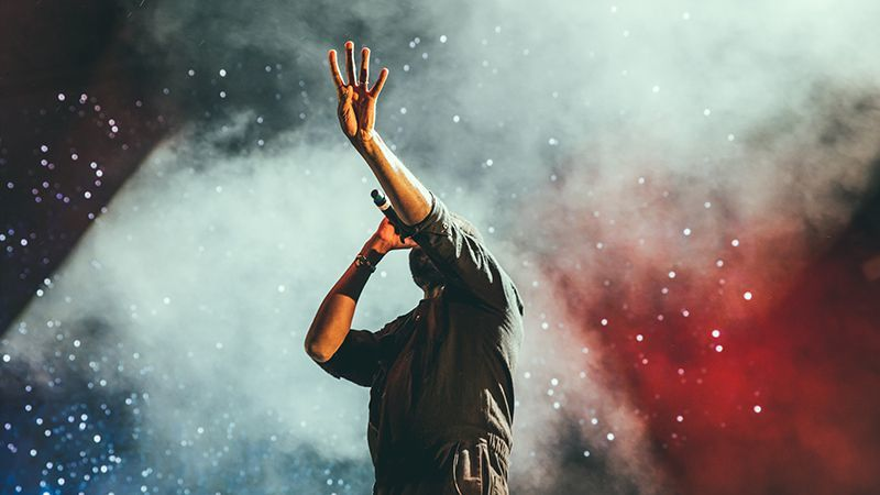 Zingende man steekt hand op in een wolk van licht